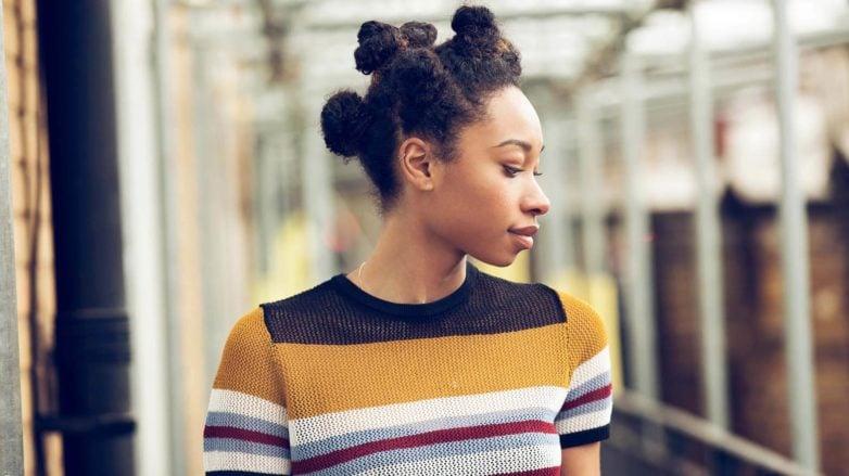 Modelo posa usando bantu knots em seu cabelo afro