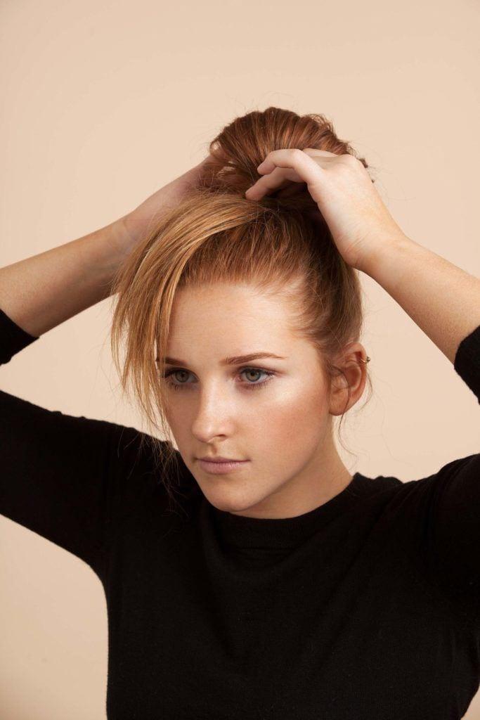 Mulher com cabelos ruivos e coque de laço