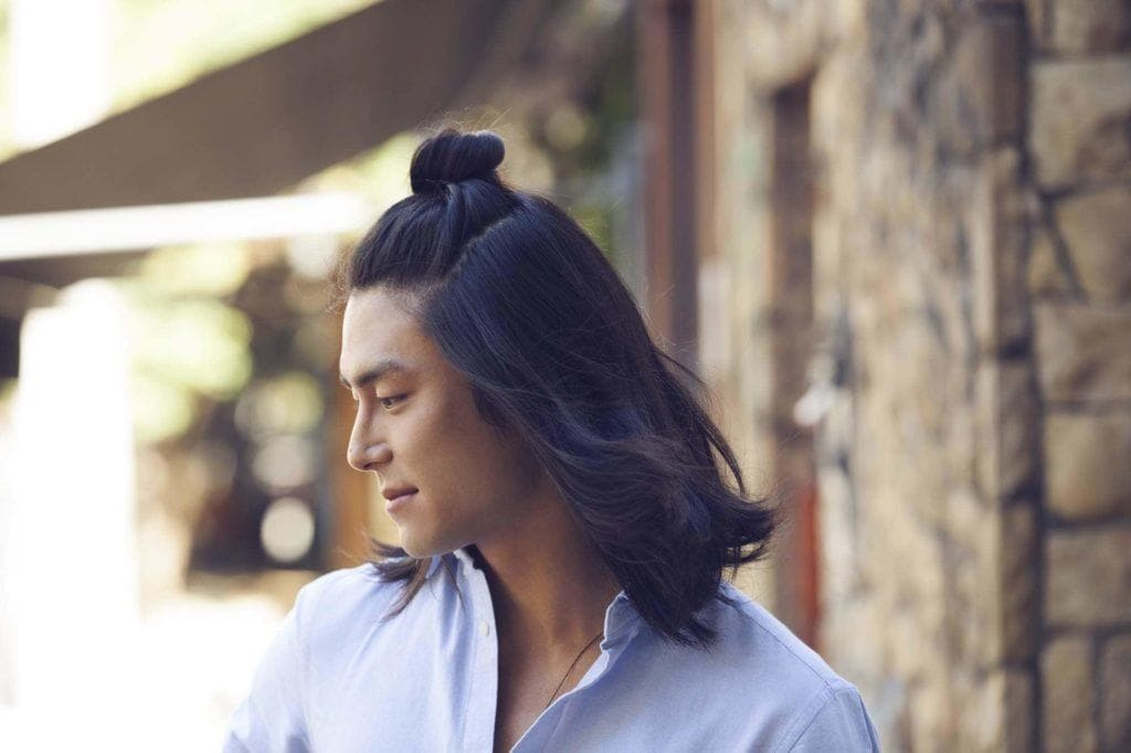 Homem com cabelo longo com coque semipreso