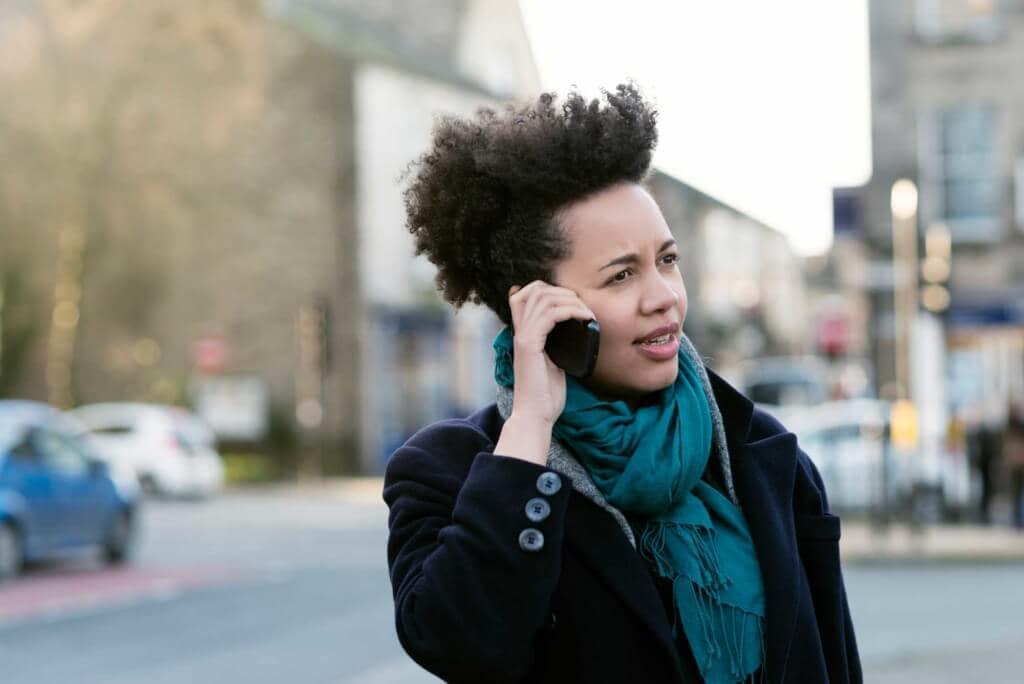 Mulher fala ao telefone com cabelo cacheado com a ajuda da fitagem