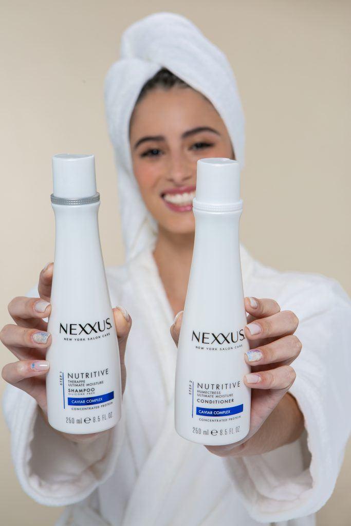 Mulher om toalha na cabeça segurando shampoo e condicionador