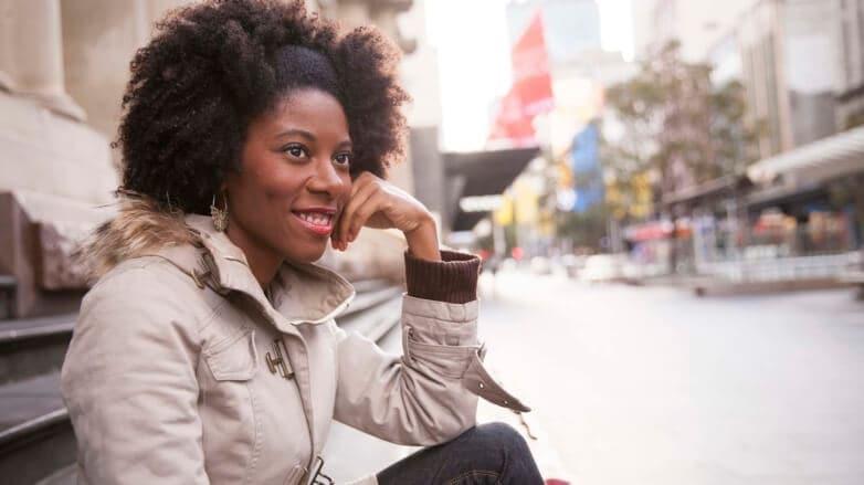 Mulher usa trança presa como dica de penteados afro