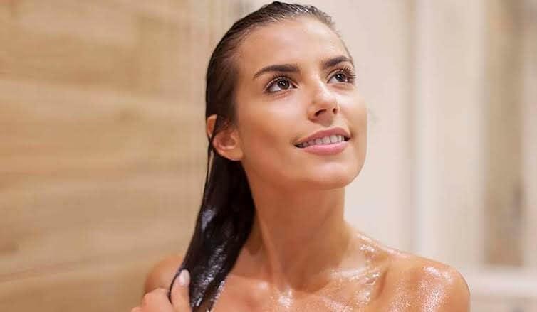 Lavar o cabelo com água mineral: mulher morena tomando banho