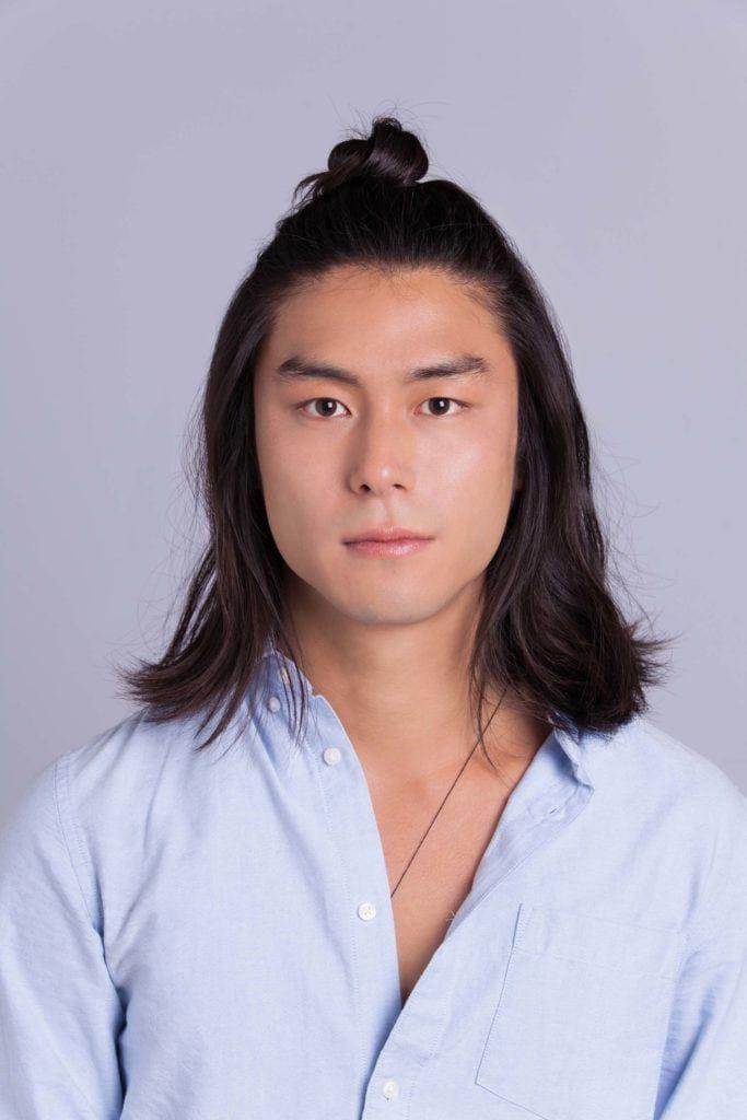 Homem com cabelos pretos e longos com coque samurai