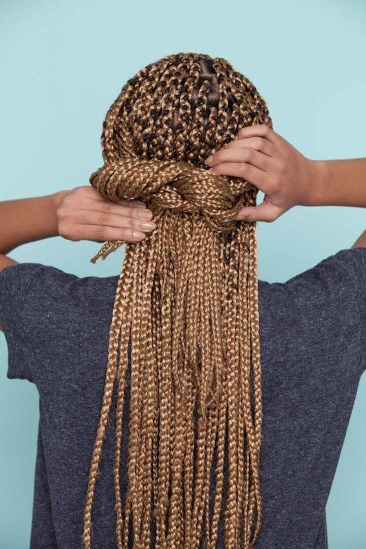 Mulher mostra como finalizar o penteado, como fazer uma franja com nó duplo em cabelo trançado