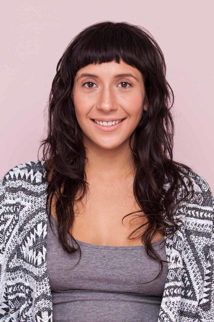 Mulher com cabelos pretos ondulados e franja