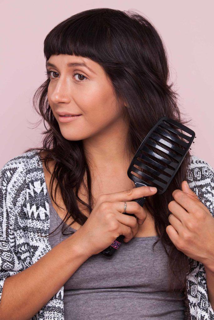 Mulher penteando os cabelos pretos ondulados com franja