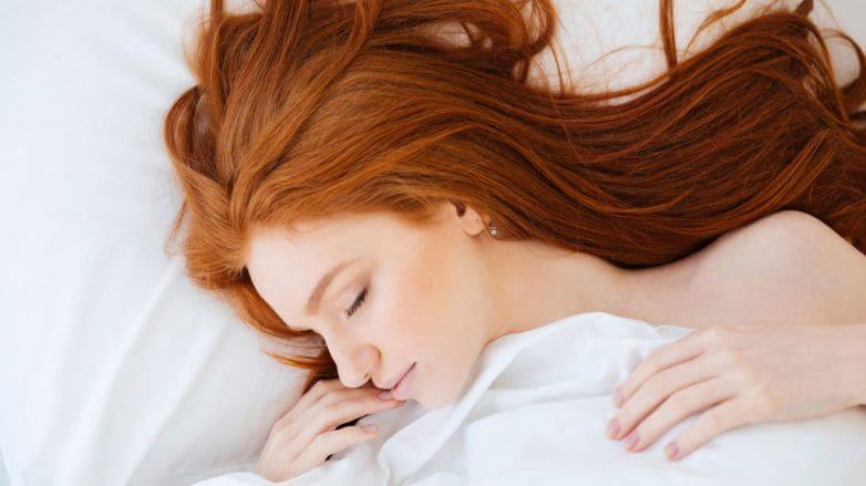 Mulher ruiva adormecida ilustra matéria sobre cuidados com o cabelo antes de dormir