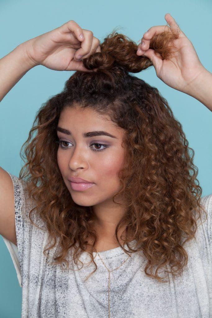 Mulher com cabelos crespos e coque no alto da cabeça