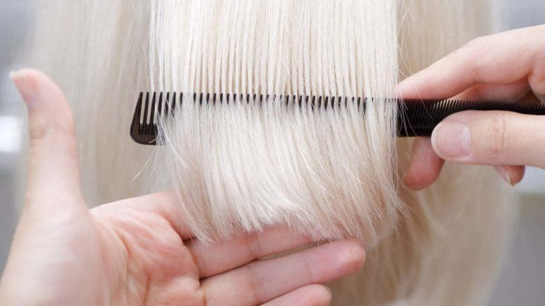 Mulher loira com cabelos lisos no cabeleireiro