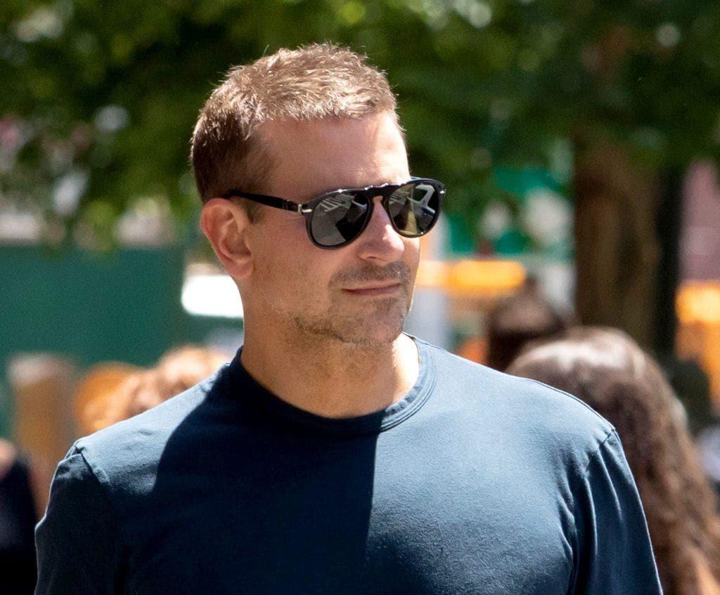 Bradley Cooper caminha ao ar livre em dia de sol. Ele usa camiseta azul marinho e óculos de sol