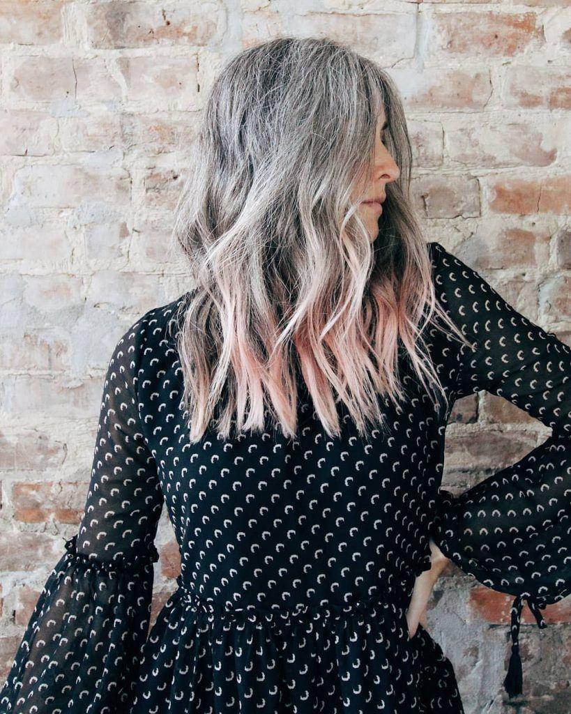 Mulher com cabelo grisalho com as pontas cor-de-rosa