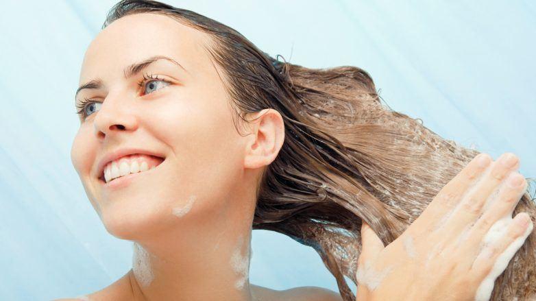 mulher passando creme no cabelo molhado