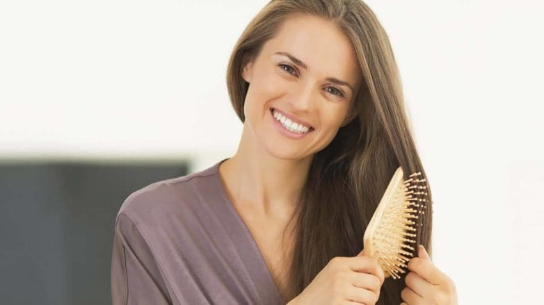 Mulher usa escova raquete enquanto veste roupão lilás e sorri.