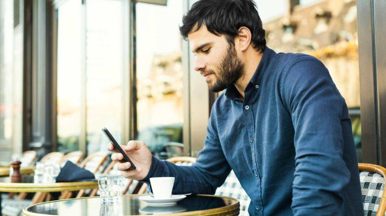 homem com entrada olha para o celular