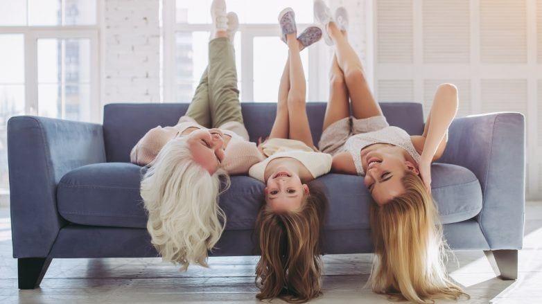 Mãe, vó e filha brincam no sofá e deitam de cabelos para baixo