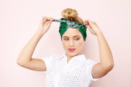 Mulher usa blusa branca e dá o nó no lenço verde para ensinar a a fazer um penteado com bandana cheio de estilo