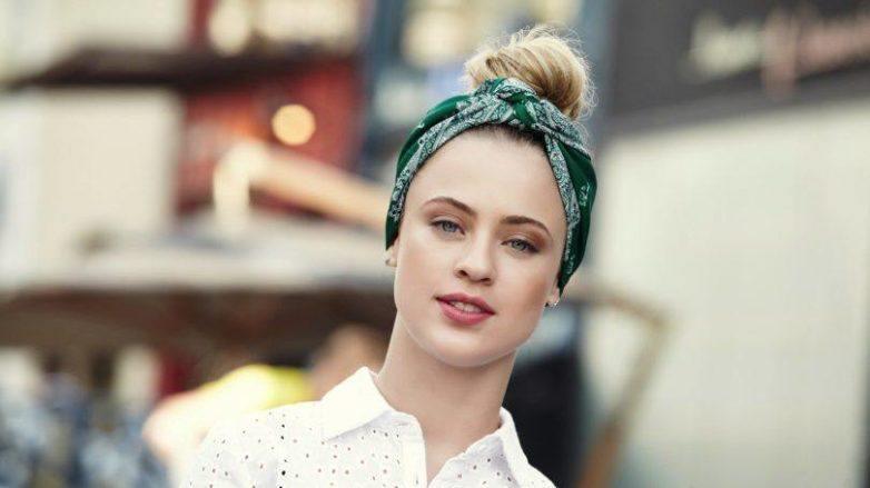 Mulher loira usa camisa branca e lenço verde e ensina a fazer um penteado com bandana cheio de estilo
