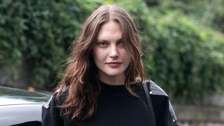 Mulher com cabelos castanho-claro compridos e ondulados