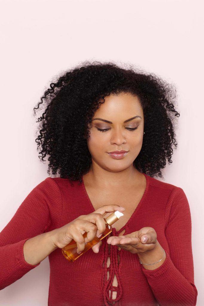 Mulher com cabelo afro passando produto nos cabelos