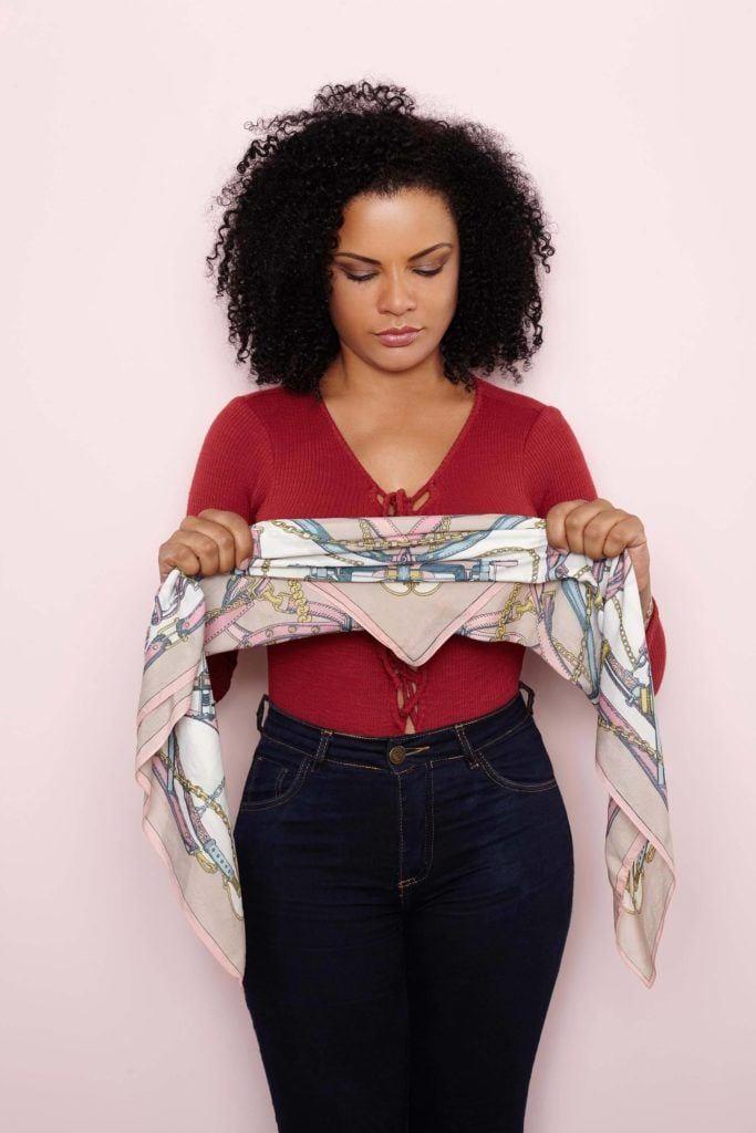 Mulher com cabelo afro segurando um lenço