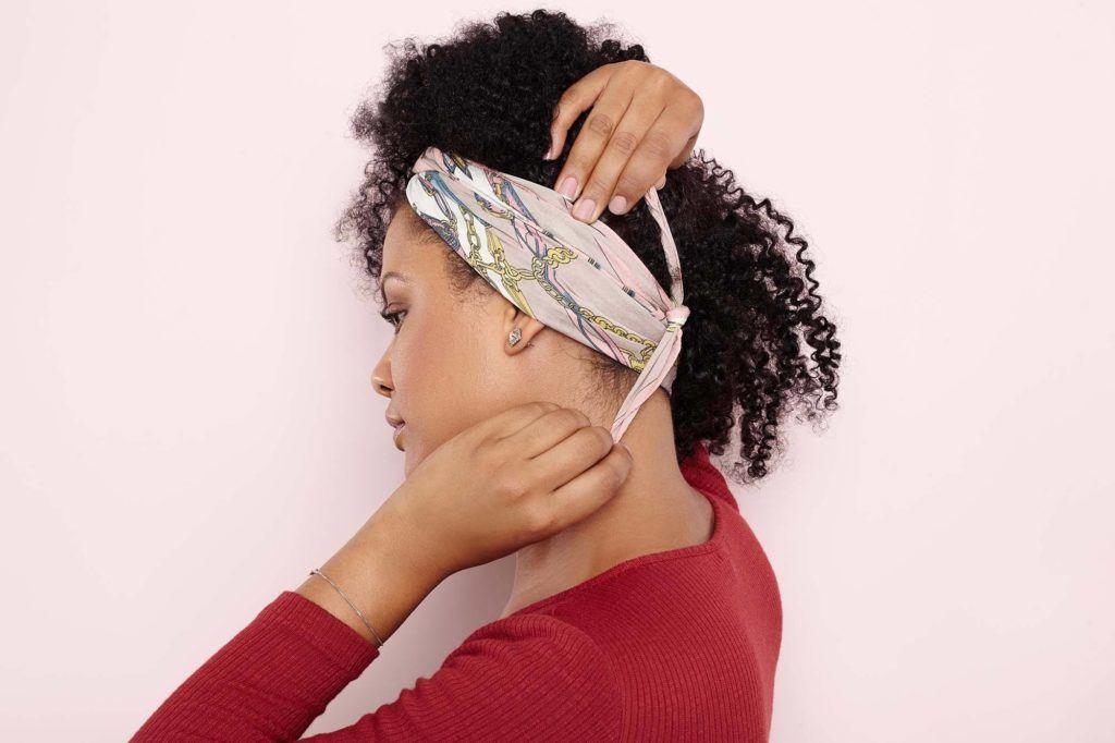 Mulher com cabelo afro amarrando um lenço na cabeça