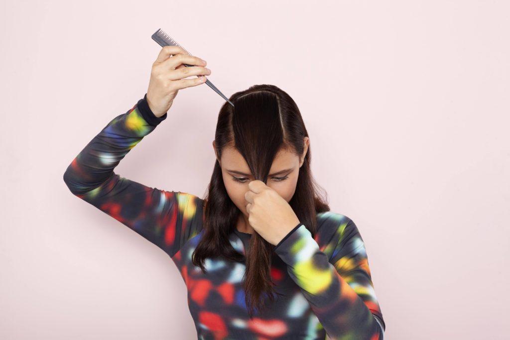 Mulher dividindo os cabelos com pente
