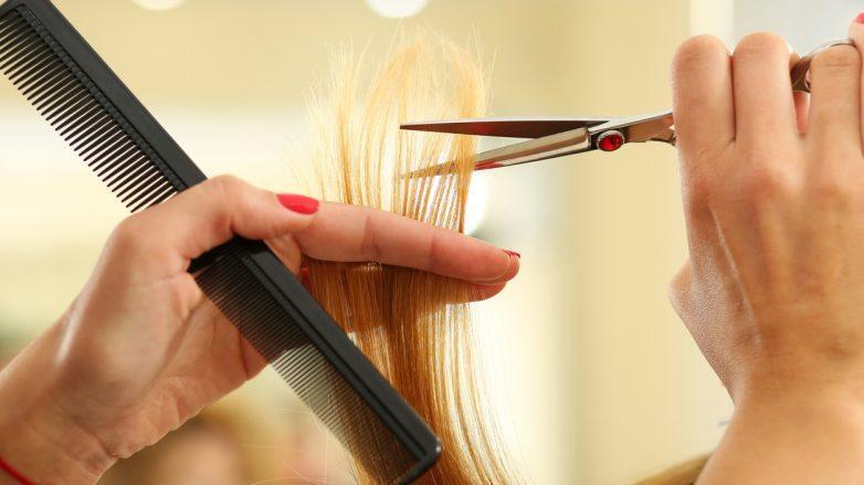 mãos com tesoura e pente cortando cabelo loiro