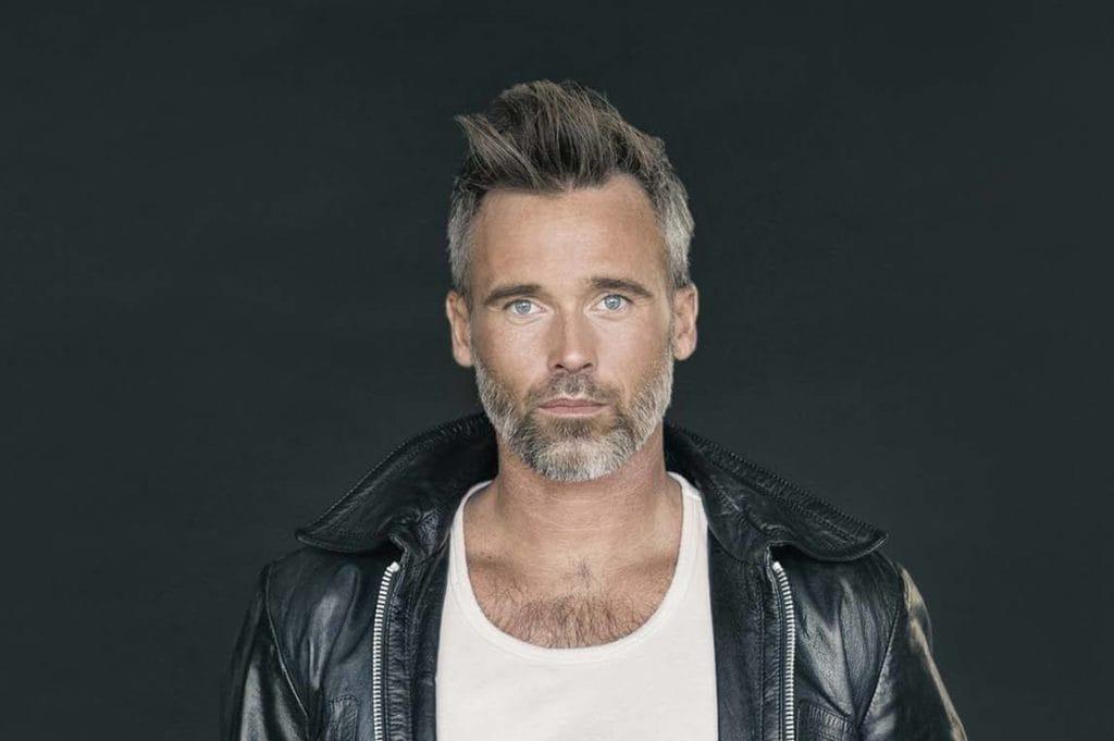 Homem com cabelo grisalho curto com topete