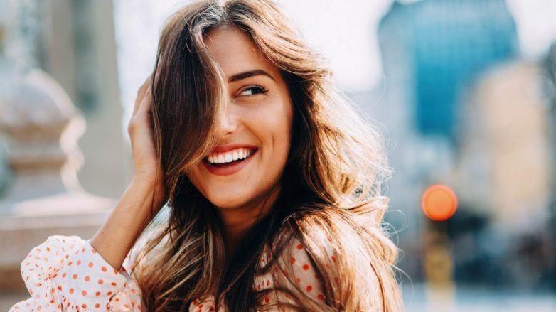 Mulher com cabelos castanho-claro longos e ondulados