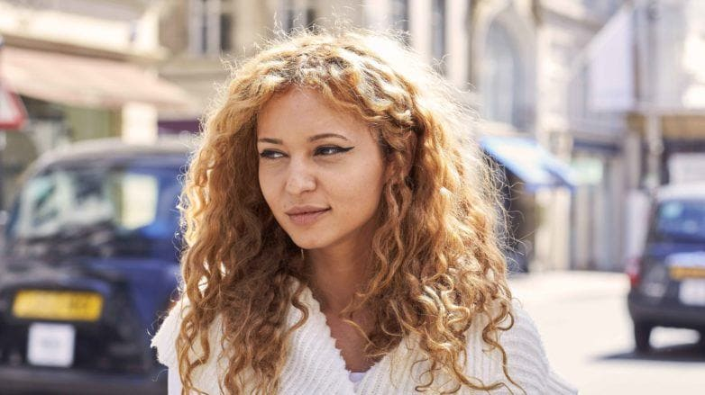 Mulher loira de cabelo cacheado ilustra a matéria sobre cortes para quem tem muito cabelo
