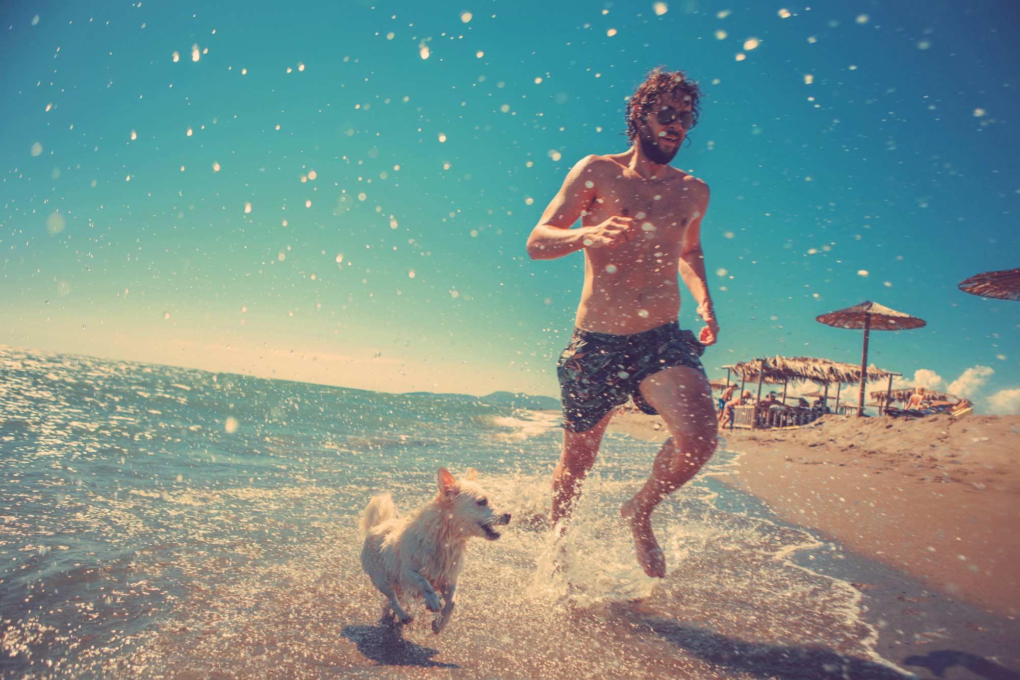 Homem e cachorro na praia ilustram matéria sobre cuidado com o cabelo masculino na praia