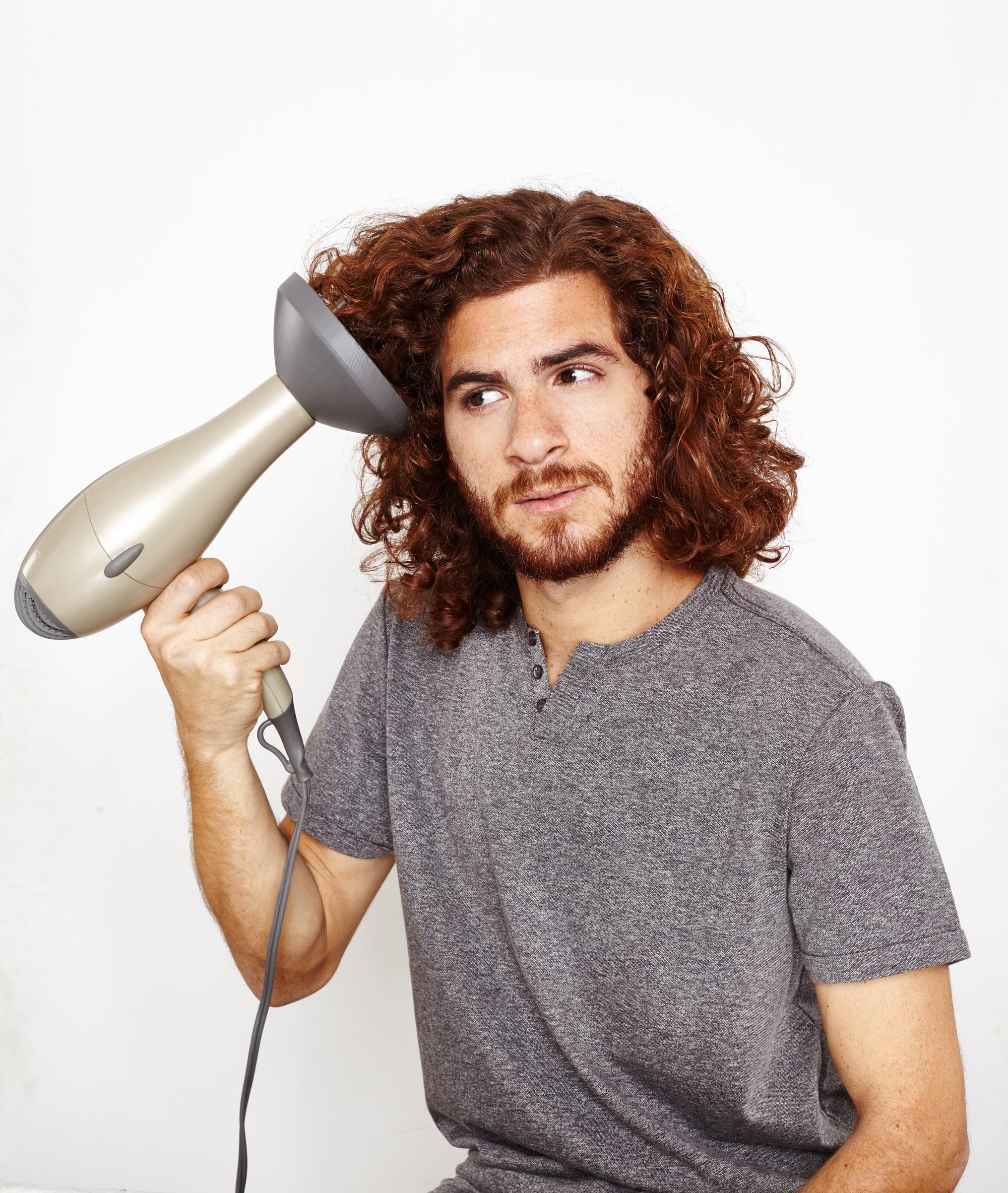 Homem usa secador com difusor para definir cachos no cabelo masculino