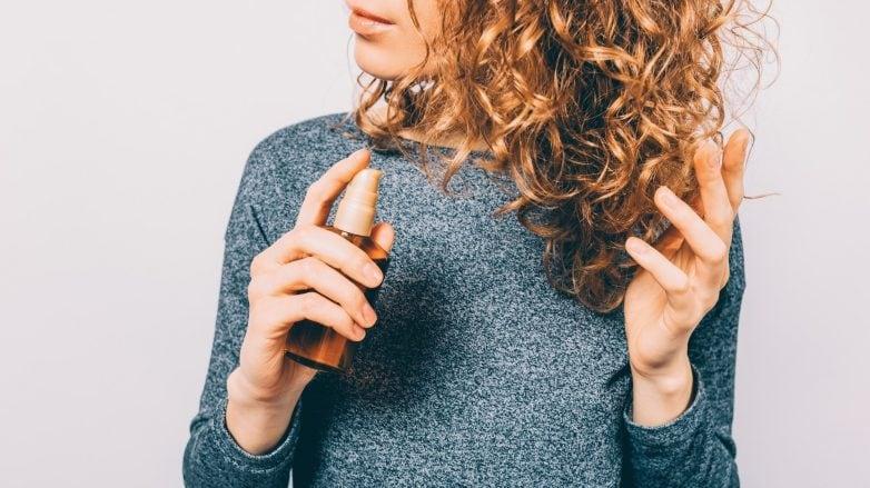 Mulher aplica óleo capilar nos cabelos cacheados