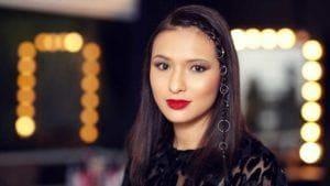 Mulher usa piercing no cabelo, e blusa preta, além de batom vermelho. Ela ilustra matéria sobre Acessórios dos anos 1990 para usar de novo