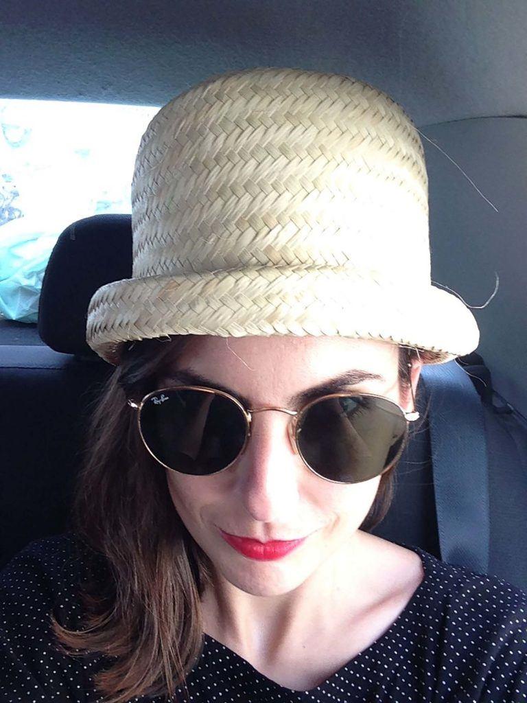 Mulher usa chapéu de palha, camiseta preta e óculos escuros, ilustrando cabelo de outro carnaval