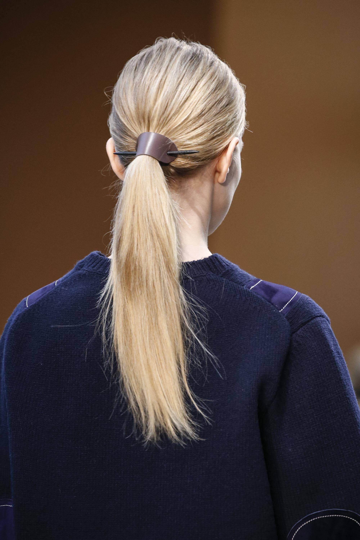 Mulher usa cabelo comprido loiro e preso, a foto a mostra de costas