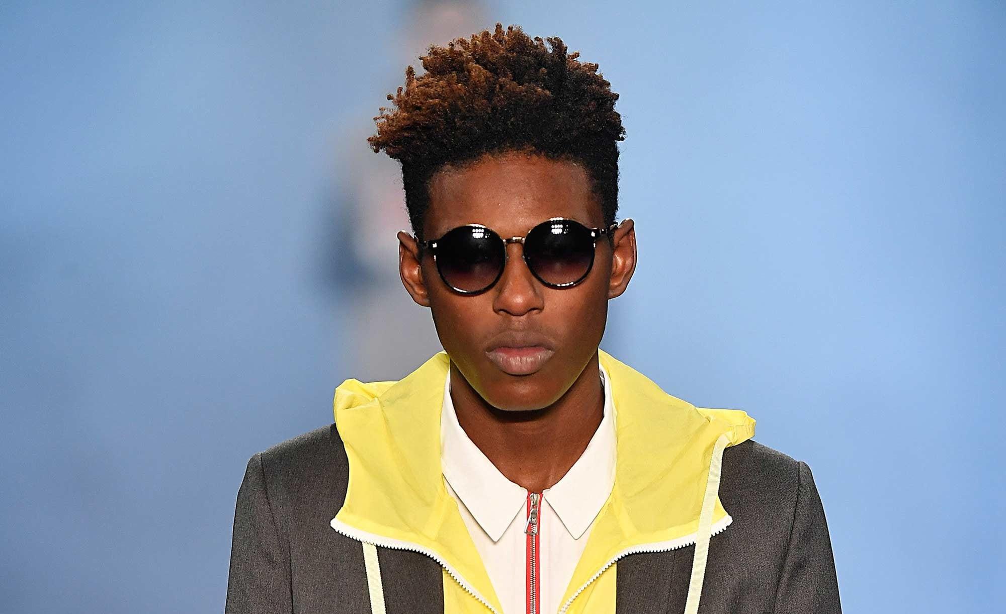 Modelo usa cabelo crespo na passarela e desfila com jaqueta amarela com gola amarela