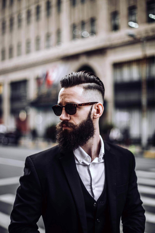 Homem com cabelos e barba pretos e fios raspados na lateral