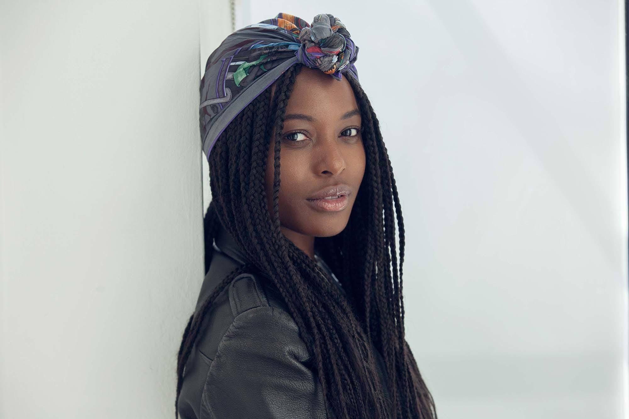 Mulher negra usa tranças e turbante, ela veste roupa preta
