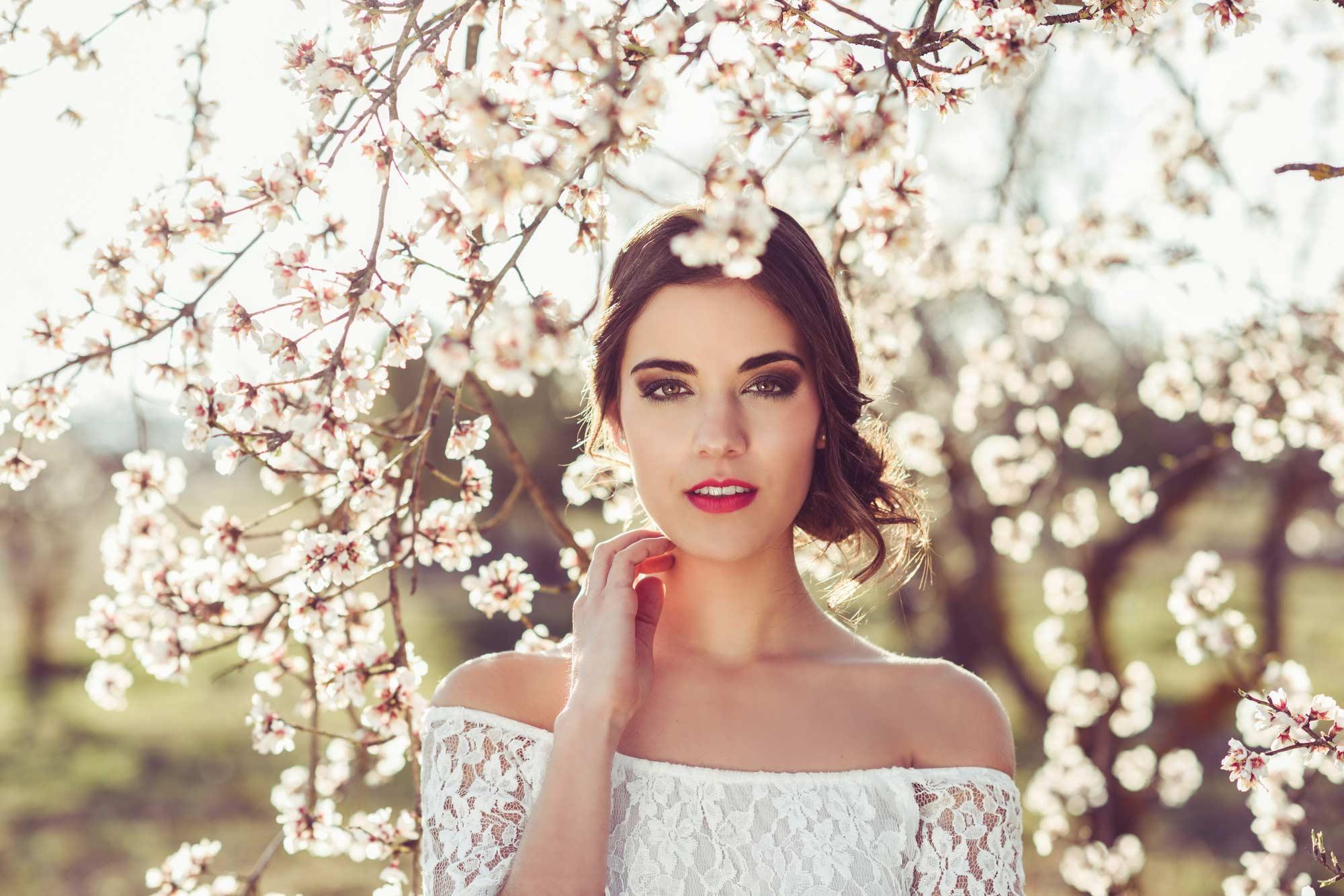 modelo com um dos penteados para afinar o rosto da noiva em um campo com flores