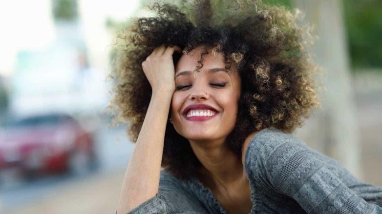 modelo com cabelo crespo ilustrando a matéria sobre touca de cetim para cabelo cacheado