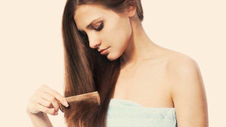 Modelo penteando os cabelos para matéria sobre afinamento capilar