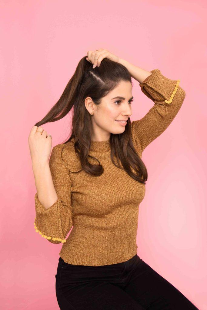 Mulher com cabelos castanho-claro lisos amarrando os cabelos