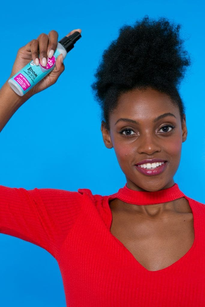 modelo de cabelo afro com penteado moicano aplicando o Spray Seda Boom Day After