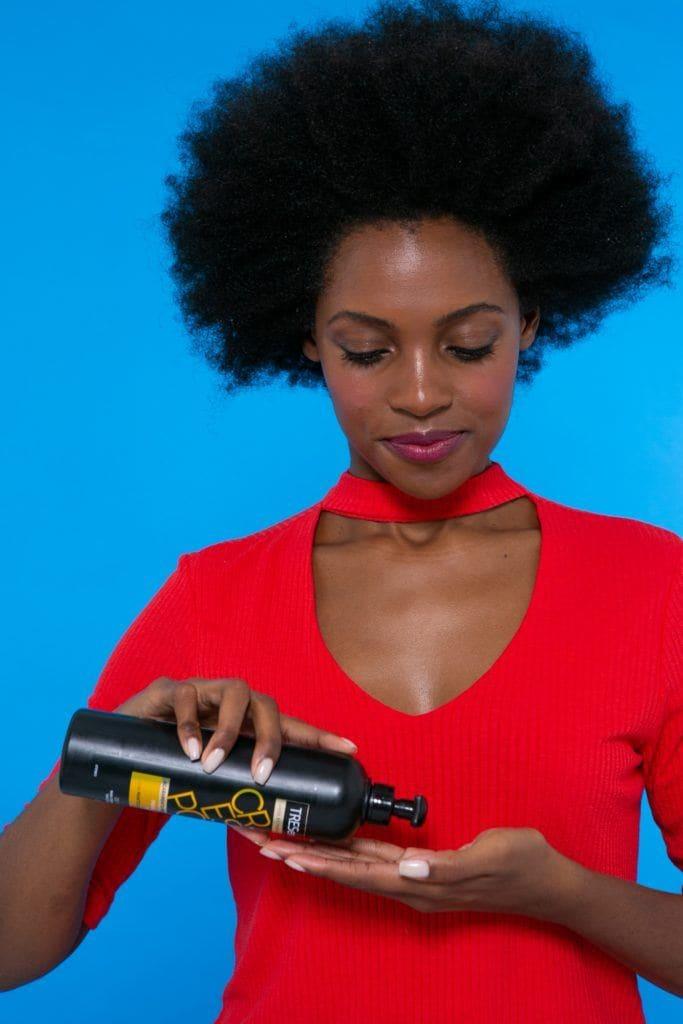 modelo de cabelo afro aplicando o Creme de Pentear TRESemmé Crespos