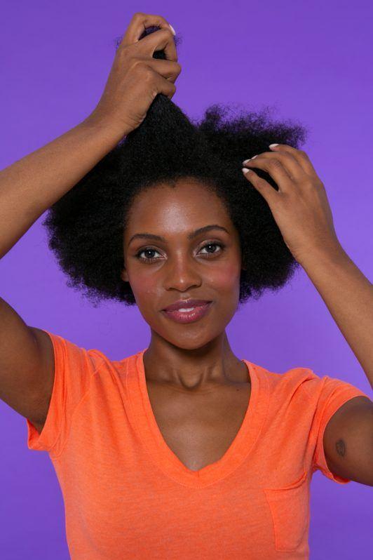 modelo de cabelo crespo separando uma mecha frontal do cabelo