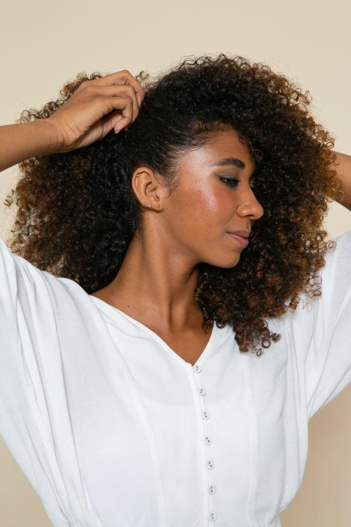 Modelo penteia a lateral dos cabelos para fazer o preso na lateral com o cabelo solto