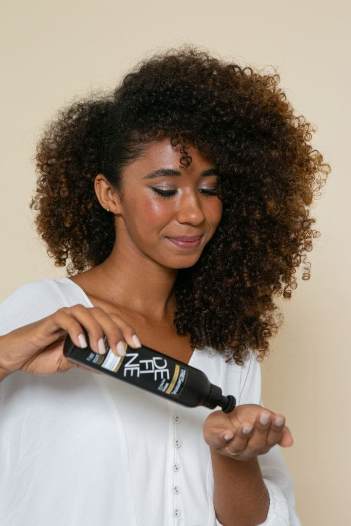 Modelo aplica produto para fazer o preso na lateral com o cabelo solto