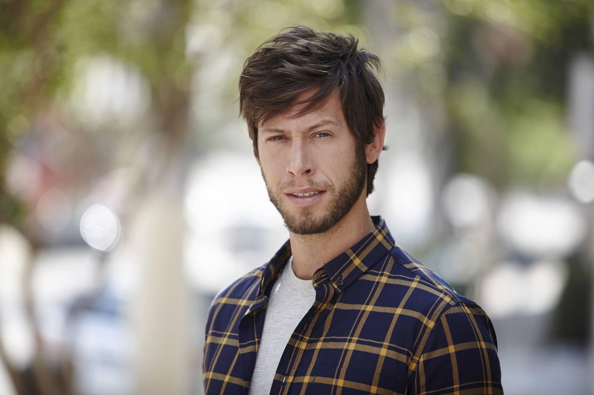 Homem com camisa xadrez e cabelo com franja desfiada